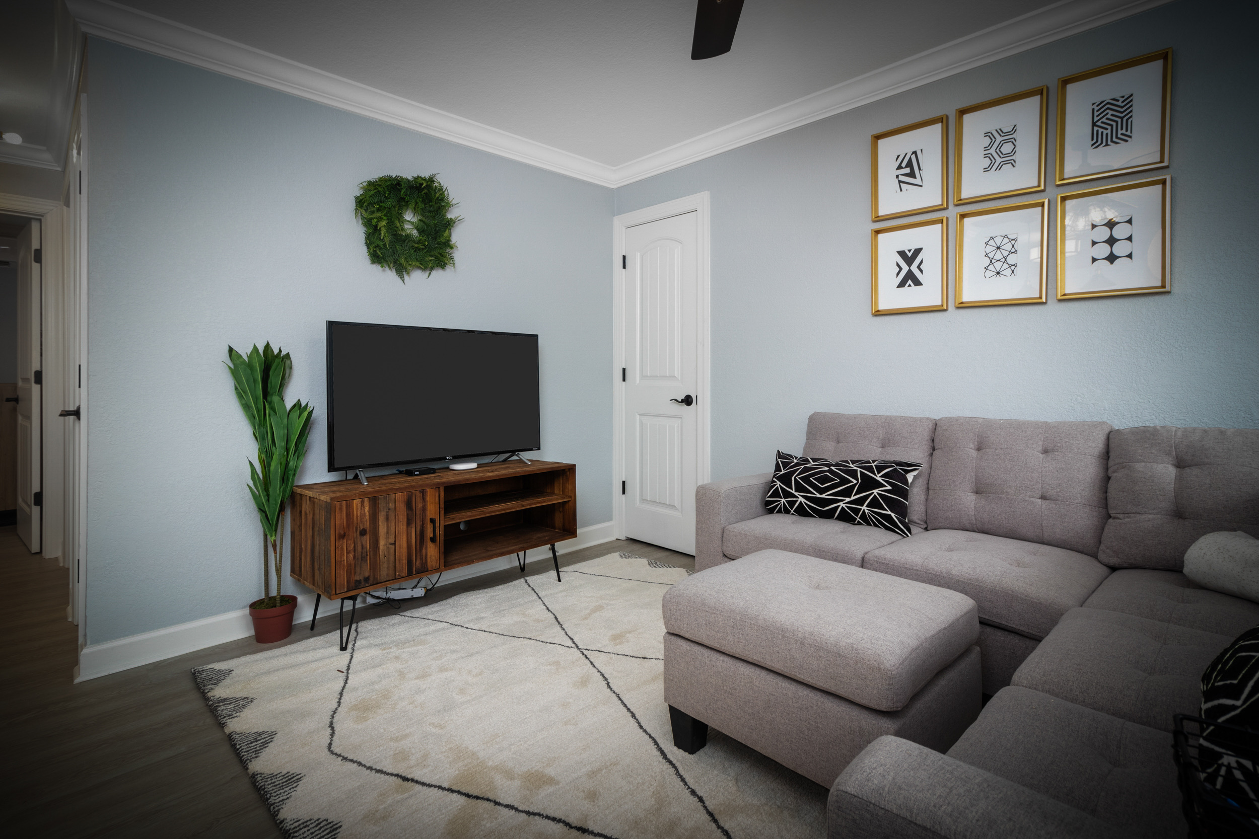 living room with a grey couch and green wreath hanging on the wall