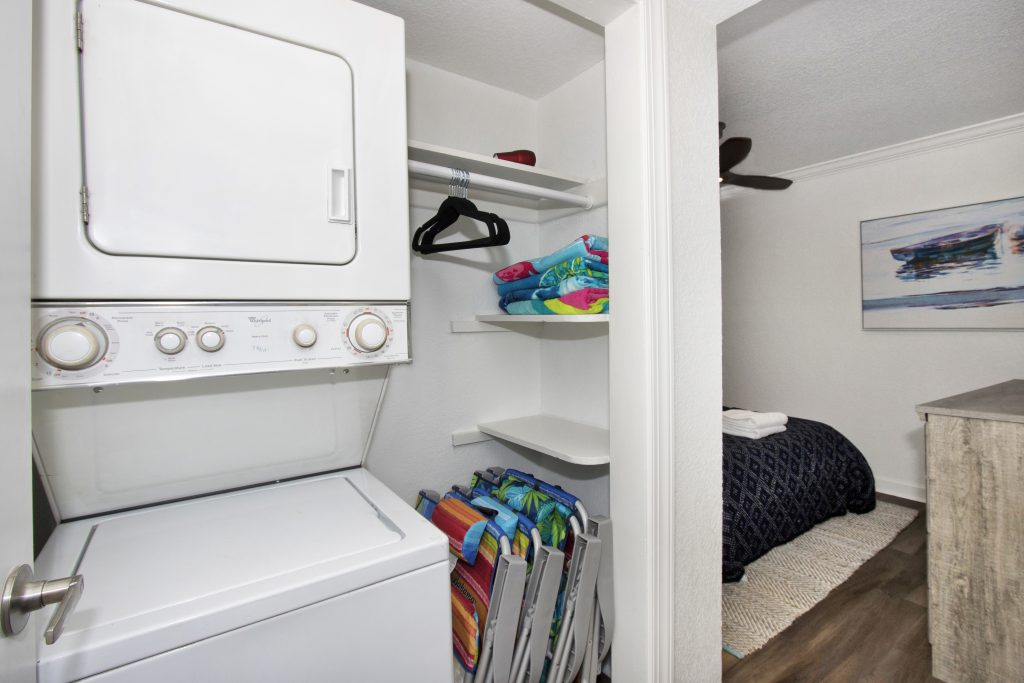 white washer and dryer with beach equipment leaned next to it