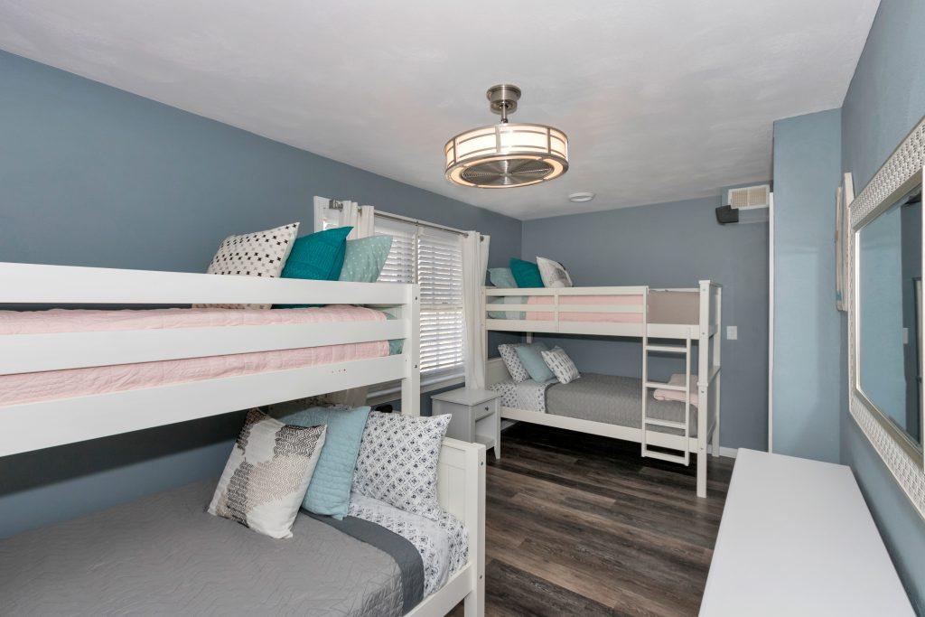 two sets of bunk beds with grey and pink bed sheets