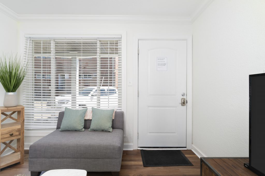 back of the front door with a grey window seat to the left
