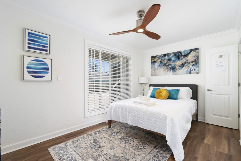 corner view of white bed with blue and gold pillows in a bedroom