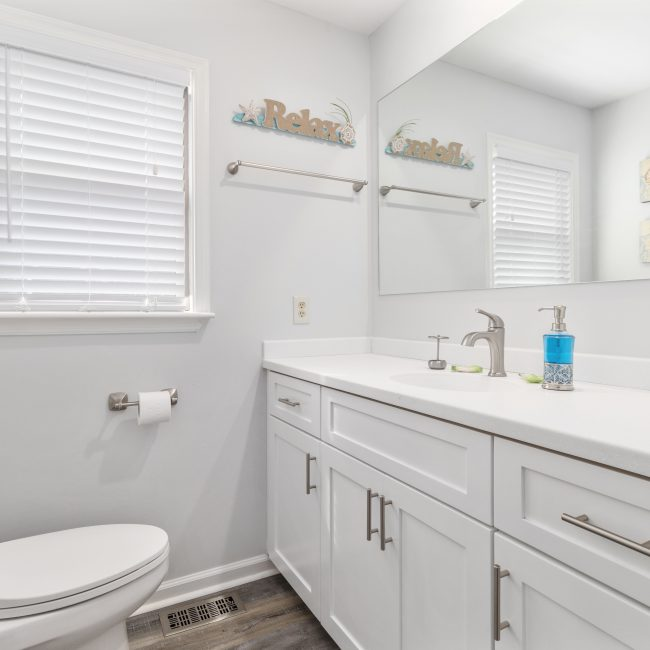bathroom with white cabinets, counter sink, and a sign that says Relax