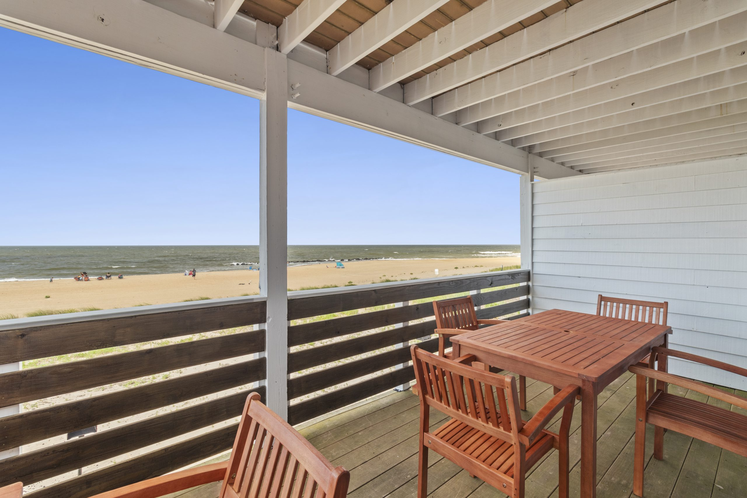 view from a deck with wood patio furniture and view of the beach
