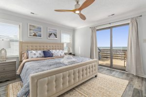 bedroom with a beige bed frame and view of the beach