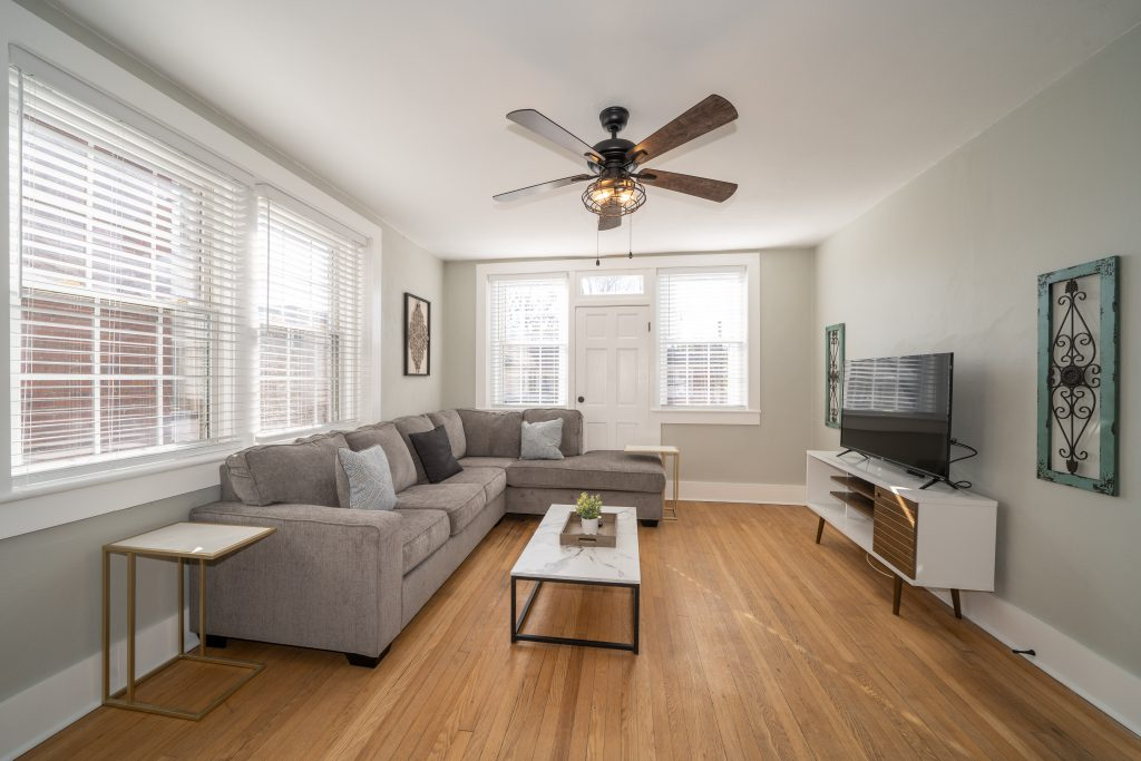 living room with grey couch, ceiling fan, and tv