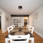 dining room with a white and brown dining table and a clock on the wall