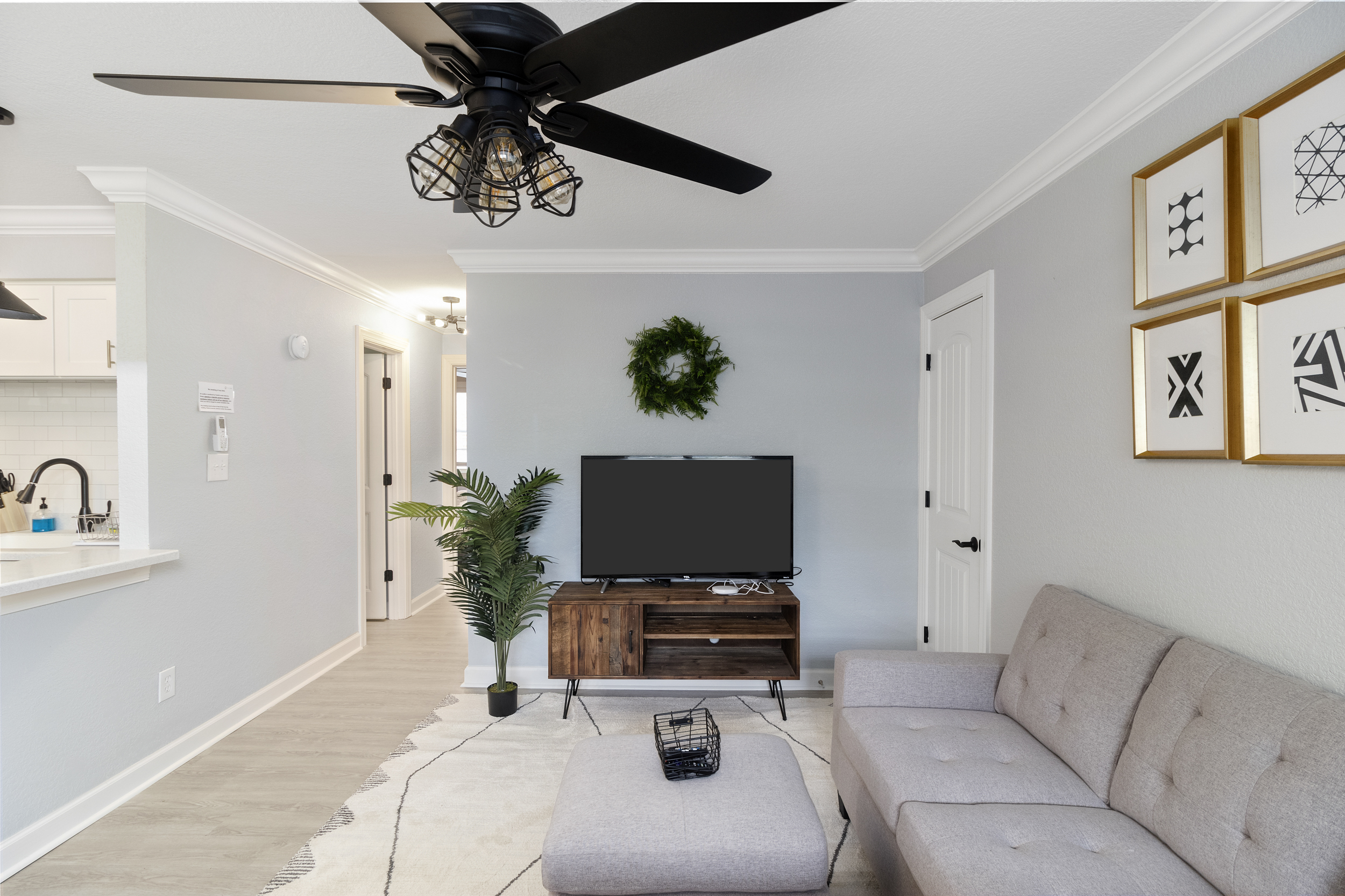 living room with a tv and green wreath hanging on the wall