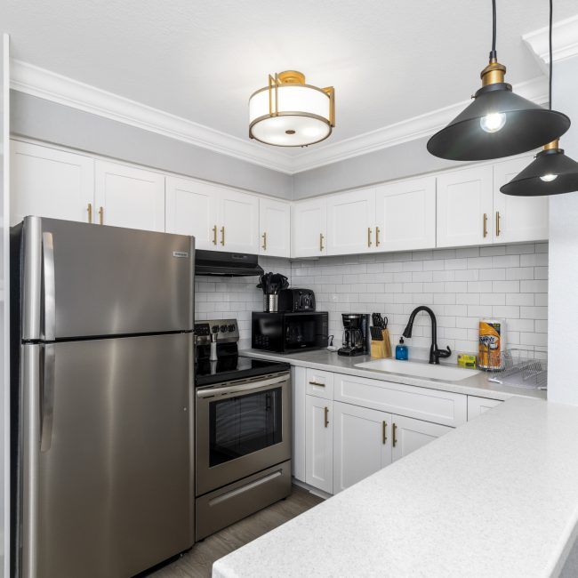 a white kitchen with stainless steel appliances