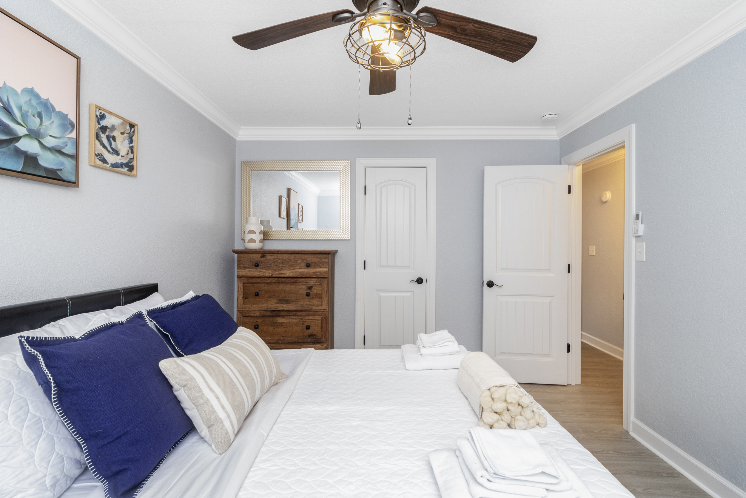 well made bed with blue pillows, brown dresser, and open bedroom door
